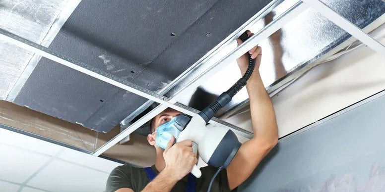 worker cleaning out ducts in a home