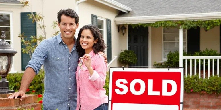 man and woman standing in front of the house they sold holding keys